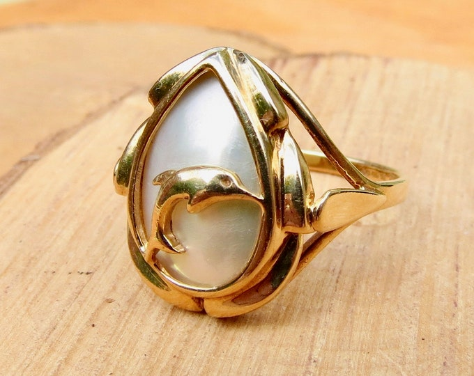 A 9k yellow gold mother of pearl dolphin ring.
