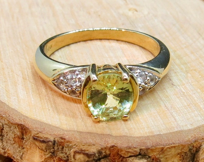 A vintage 9K yellow gold peridot solitaire ring with white stone accents.