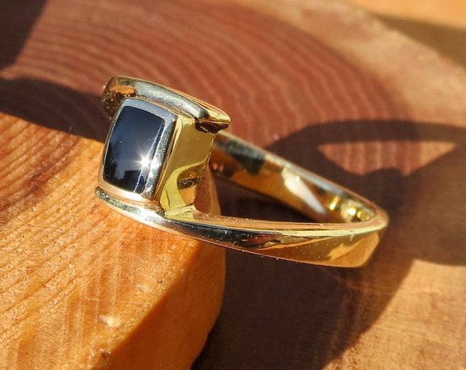 A vintage 9K yellow gold & black onyx ring