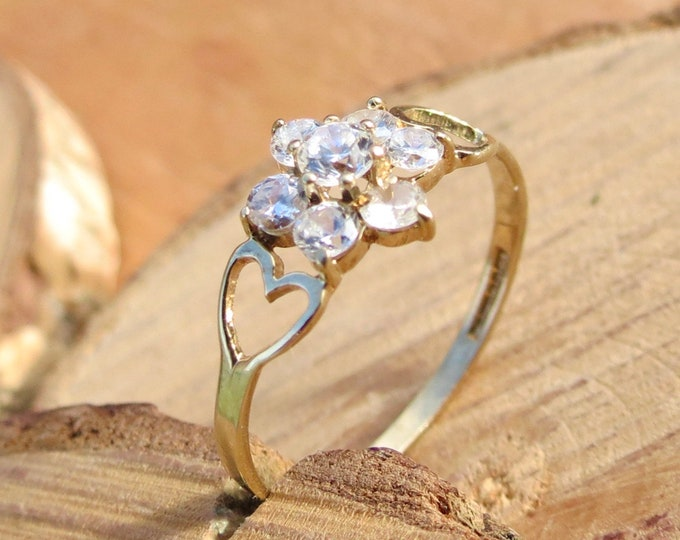 Gold topaz ring. A 9k yellow gold ring has 7 round cut white topaz set in a cluster daisy setting