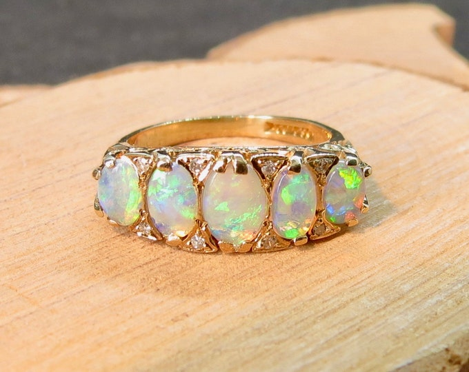 Gold opal ring. A 9K yellow gold ring with graduated Ethiopian welo opals with diamond accents.