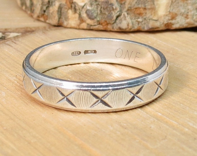 Silver band ring with decorative design.
