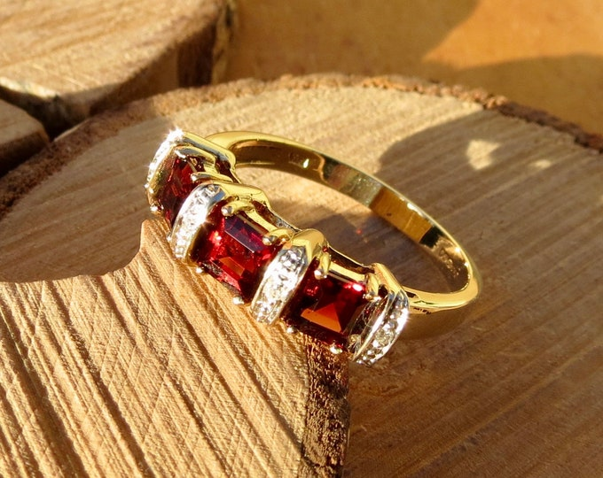 A vintage 9K yellow gold ring, with a trilogy of square cut red garnets and old mine cut diamond accents.