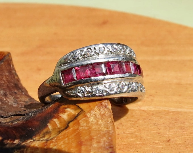 Gold ruby ring. an 18K white gold ring with 1/2 Carat of square cut rubies & white topaz accents.