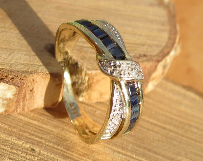 Gold sapphire ring. A 9K yellow gold sapphire and diamond crossover ring.
