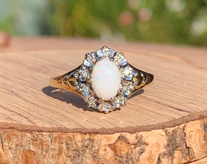 Gold opal ring. A 9k yellow gold opal cabochon ring with a diamond halo.