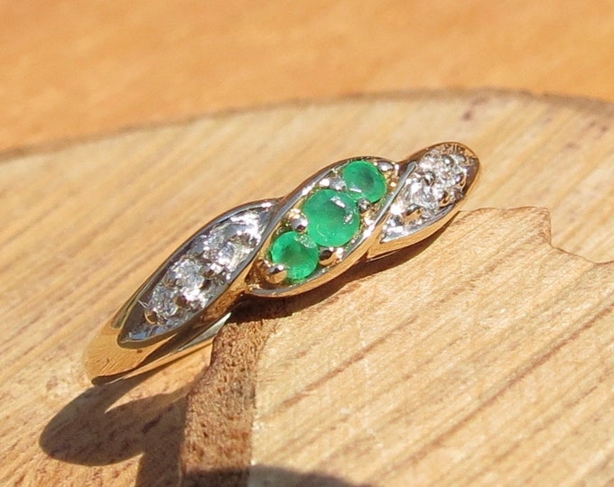 Gold emerald ring. A 9k yellow gold emerald trilogy ring with diamond accents.
