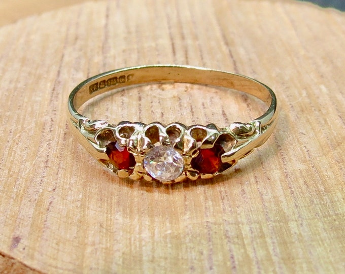 Garnet gold ring. A 9K yellow gold cubic zirconia and red garnet triple ring.