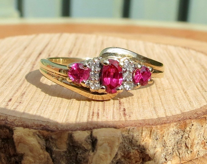 9K yellow gold ring, with a trilogy of graduated rubies and diamond accents