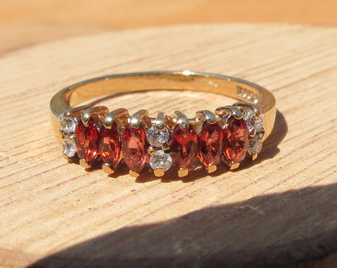 Gold CZ ring. A 9k yellow gold marquise cut red and white cubic zirconia ring