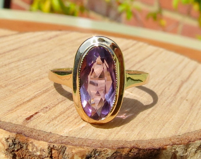 A vintage 9k yellow gold oval cut amethyst ring