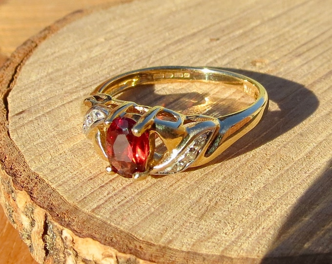 A vintage 9K yellow gold oval red garnet and diamond ring