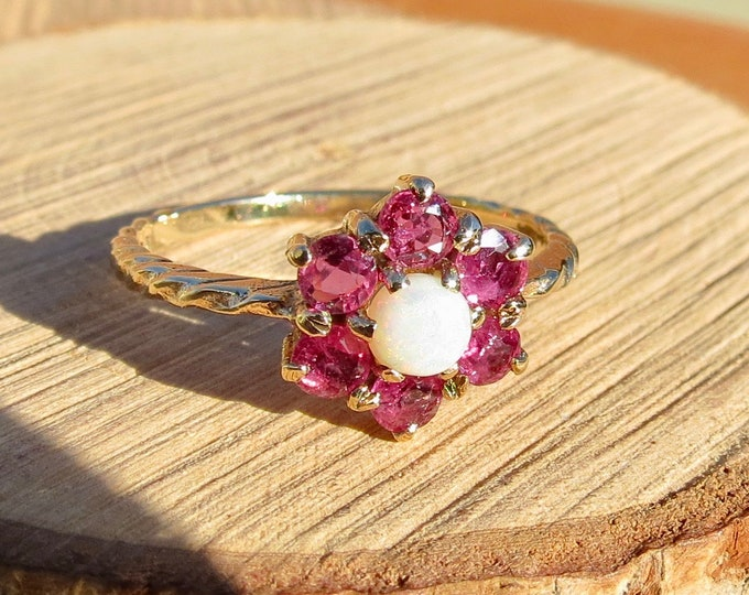 A 9K yellow gold red ruby and opal ring.