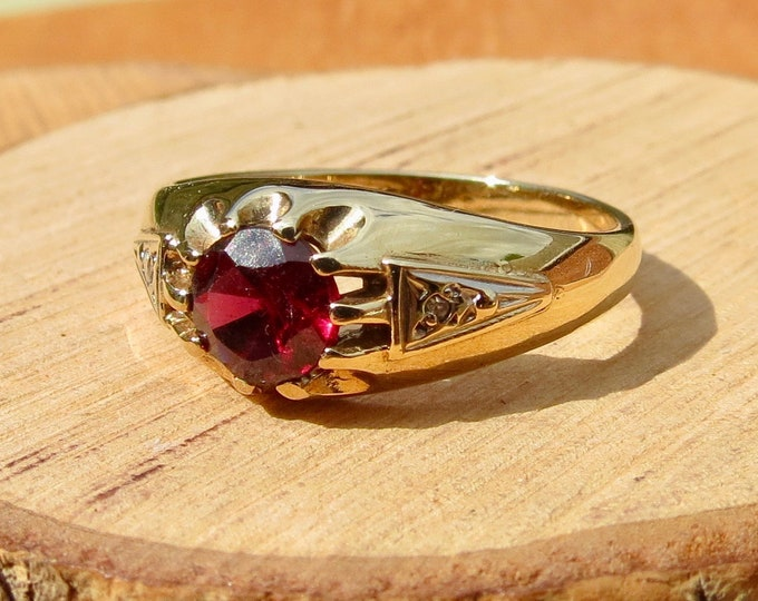 Gold rubellite ring. A 9K yellow gold solitaire rubellite and diamond ring