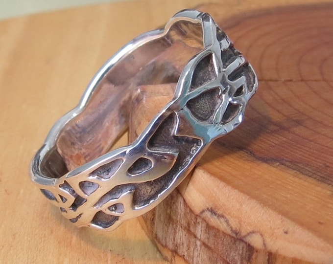 Silver ring, band,  with decorative design.