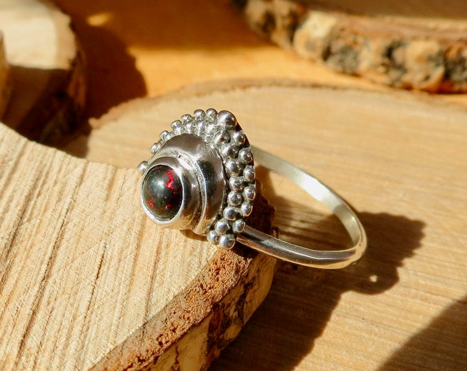 A petite silver ring with half millibead oval design and bezel set black opal.