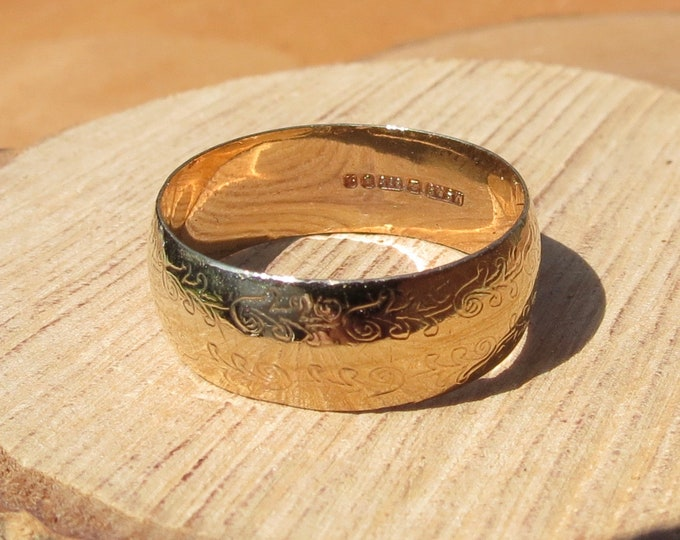 Gold wedding ring. Wide 9K yellow gold engraved court profile band.