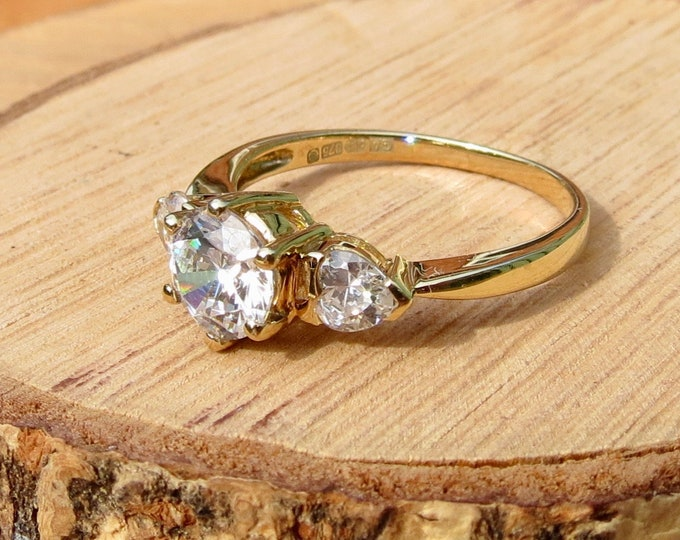 A 9K yellow gold 1.25 carat cubic zirconia heart and solitaire ring.