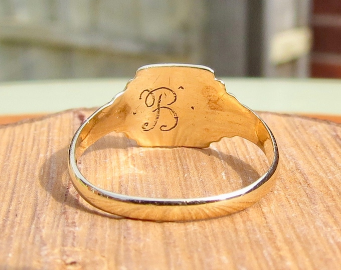 A petite 9K yellow gold decorative engraved signet ring.