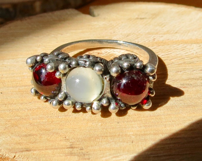 Silver ring, trilogy, synthetic moonstone and red garnet cabochon.