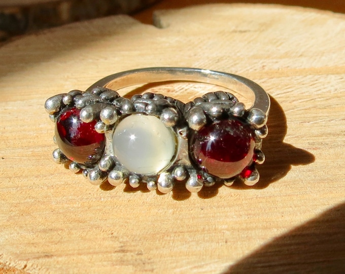 A silver, synthetic moonstone and red garnet cabochon trilogy ring.