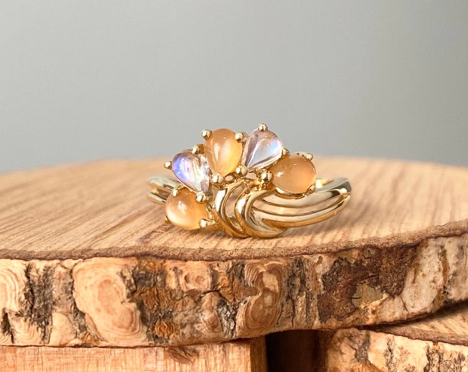 Gold multi-gem ring. A petite 9K yellow gold twin band ring with a fan of honey opals and moonstones.