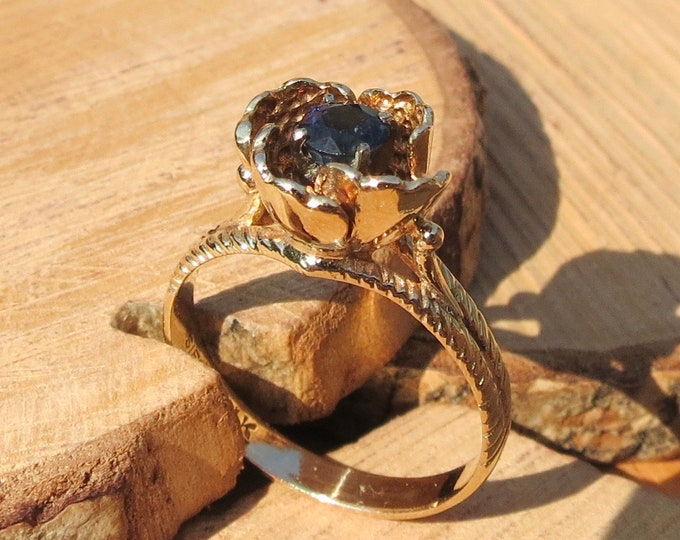 Gold sapphire ring. 14k yellow gold with blue round cut sapphire set in floral gold petals.