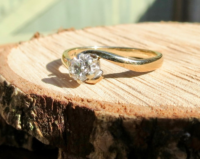 A vintage 9k yellow gold diamond solitaire crossover ring.