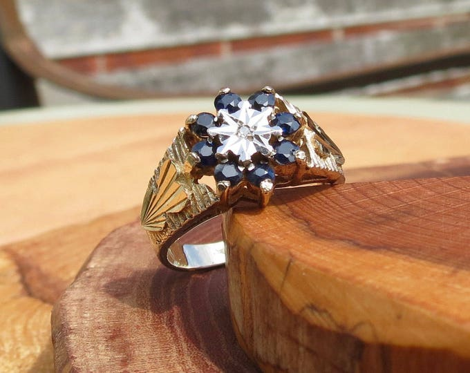 A Vintage 9K yellow gold sapphire and diamond daisy ring.