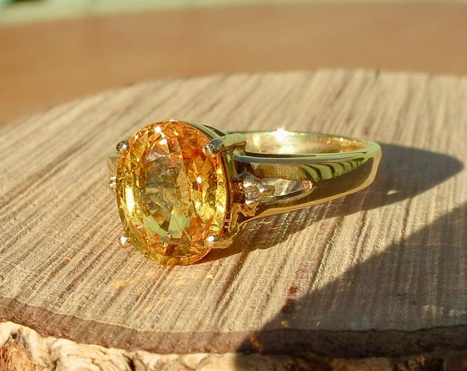 Gold yellow sapphire ring. An 18k yellow gold ring with a 2 carat oval cut yellow sapphire and diamond accents.