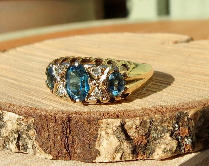 Gold topaz ring. A vintage 9K yellow gold London blue topaz and diamond trilogy ring