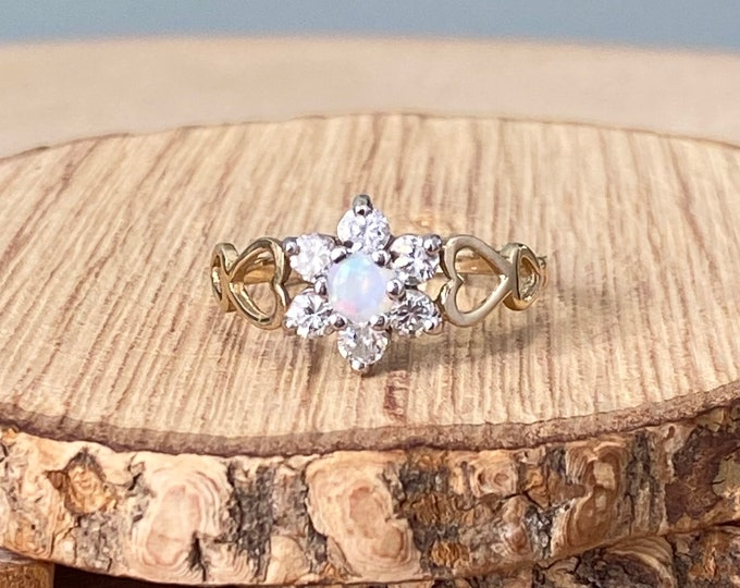 Gold opal ring. A 9K yellow gold daisy ring with a central opal and CZ accents.