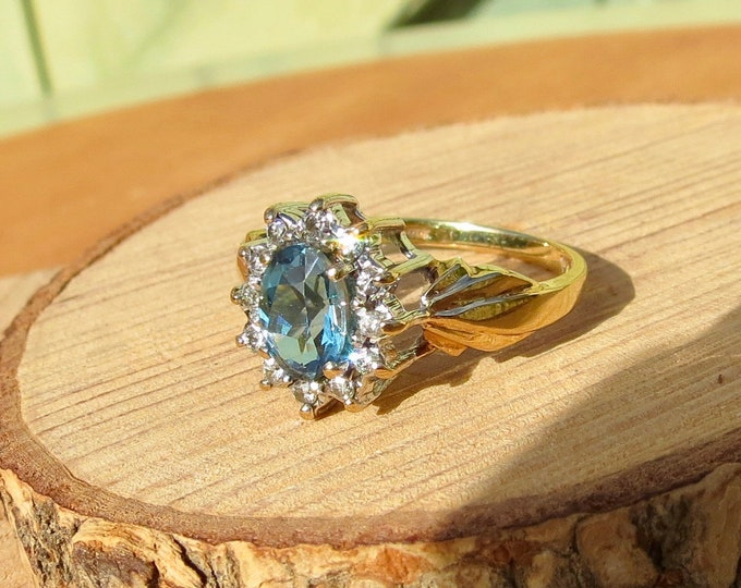Gold topaz ring. A 9k yellow gold London blue topaz and diamond ring