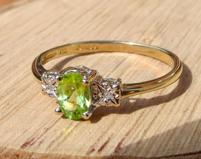 A 9K yellow gold peridot solitaire ring with diamond accents.