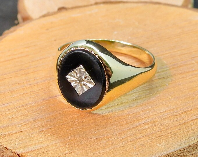 A vintage 9K yellow gold oval black onyx and diamond signet