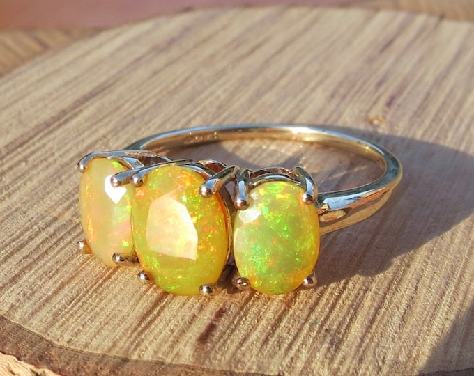 Gold opal ring. A 9K yellow gold ring with graduated fiery yellow opal trilogy.