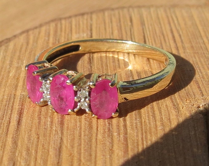Petite 9K yellow gold ring, with a trilogy of rubies with diamond accents.