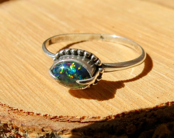 A petite silver ring with millibead collar design and bezel set black opal.