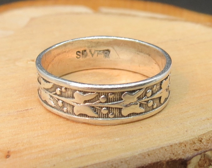A petite silver band with laurel leaf design.