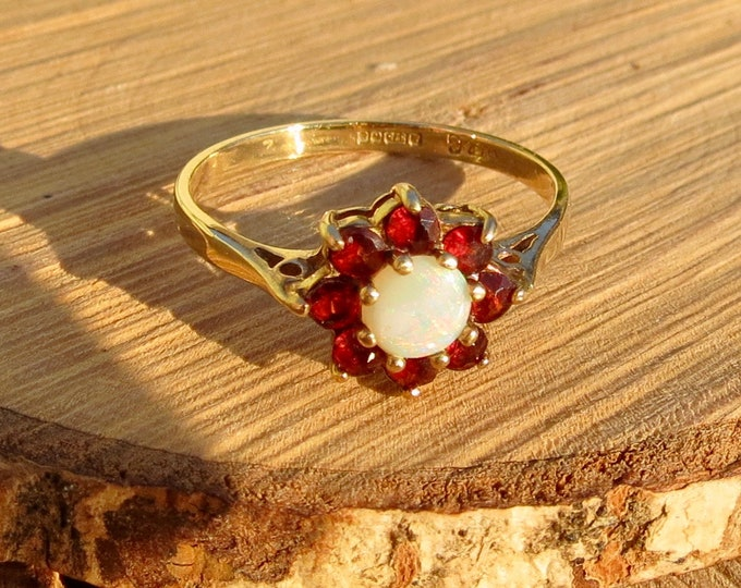 A 9K yellow gold red garnet and opal ring.
