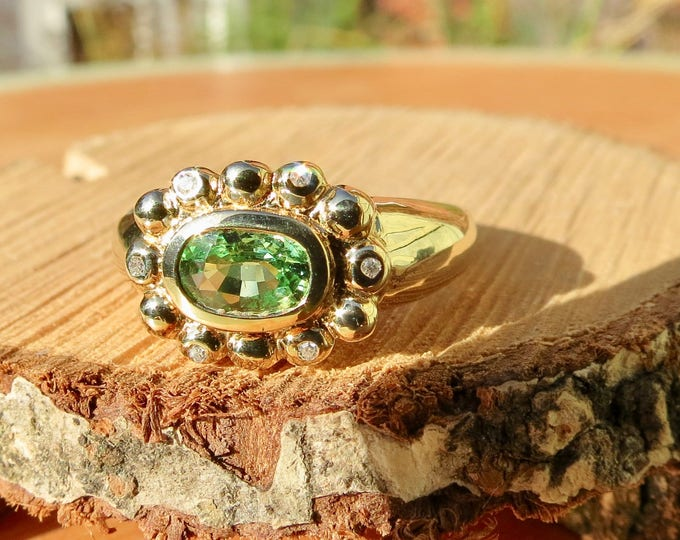 A vintage 9K yellow gold peridot ring with diamond accents.