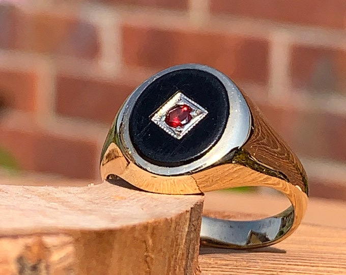 Gold signet ring. Vintage 1970s. 9K yellow gold, onyx oval with diamond shaped central plaque and a red garnet accent stone.