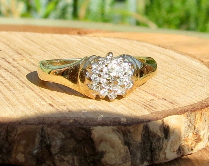 Gold diamond ring. A petité 9k yellow gold 1/6 carat diamond daisy ring.