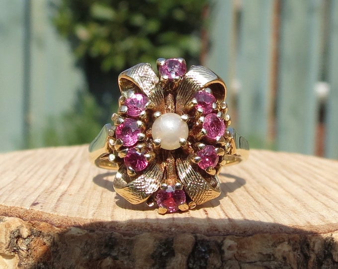 Gold ruby ring. 1960s vintage 9k yellow gold cluster ring has a central natural pearl with eight ruby accents decorated ribbons of gold.
