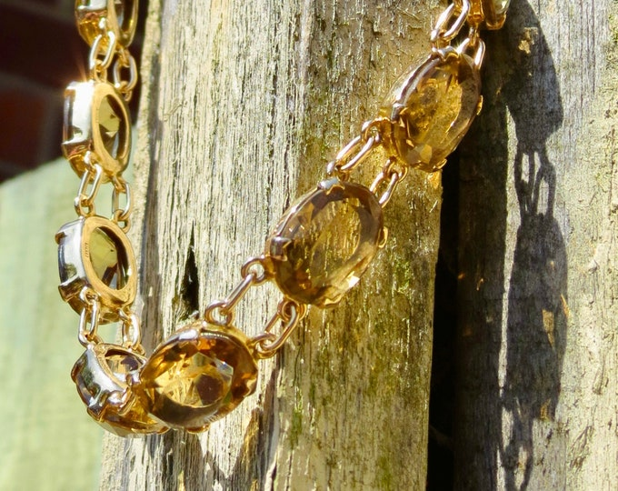 A Scottish 9k yellow gold smokey quartz bracelet with lobster claw clasp and safety chain, made in 1972. Total gemstone weight 44 carats.