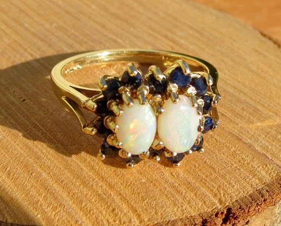 A vintage 1970's 9K yellow gold ring with twin opal cabochons and a halo of sapphire accents.