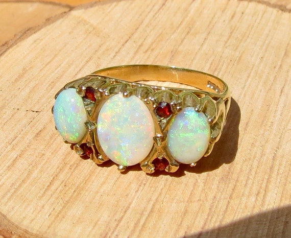 A vintage 9K yellow gold ring with a graduated opal cabochon trilogy with rose cut red garnet accents.