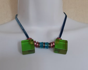 Neck or choker with block of green resin, pink rhinestone bead and blue glass bead on blue velvet