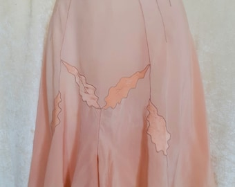 Salmon pink silk shorts with applications of satin leaves and ecru embroidery.