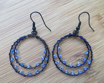 Black wire hoop earrings wrapped with blue wire and blue beads
